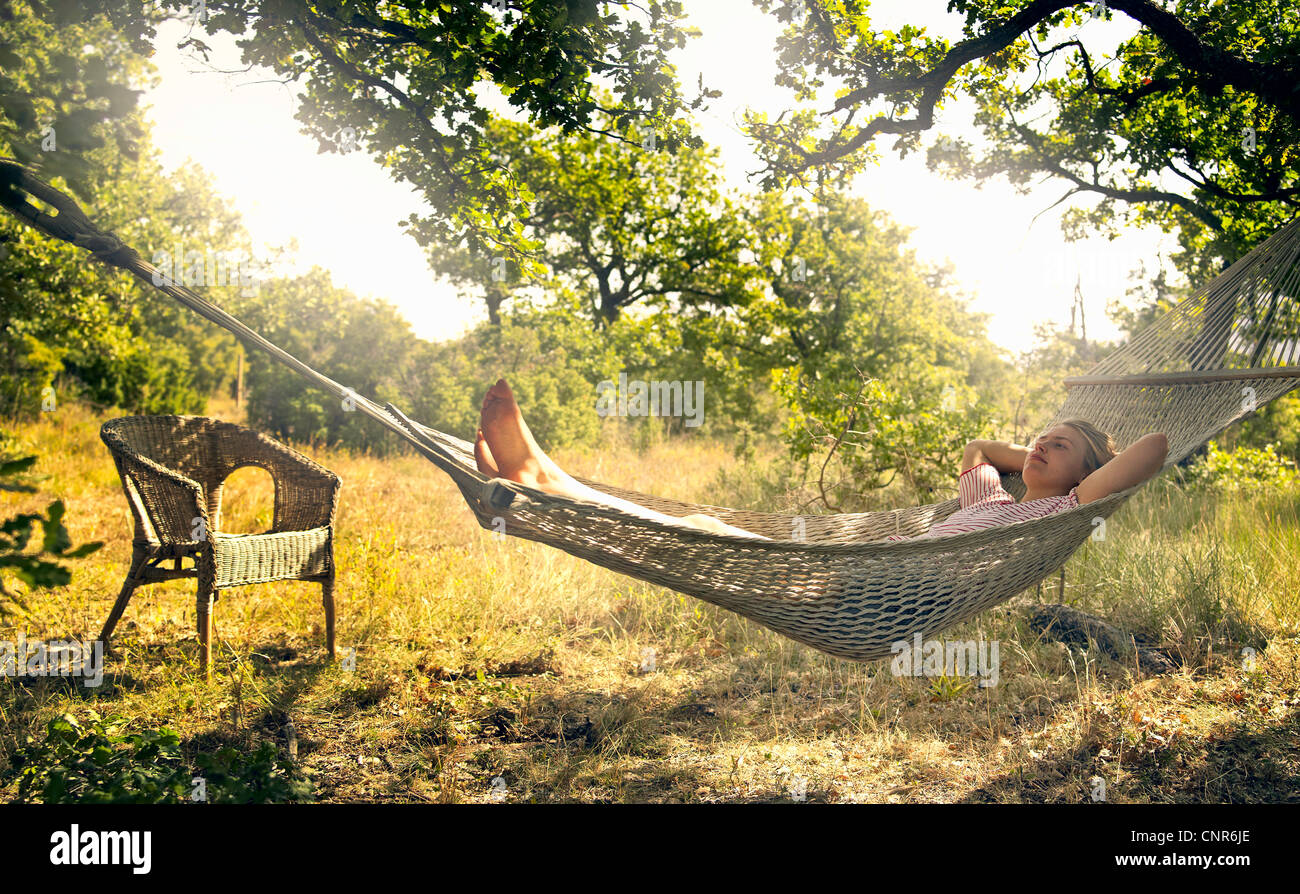 Man relaxing in hammock outdoors - Stock Image