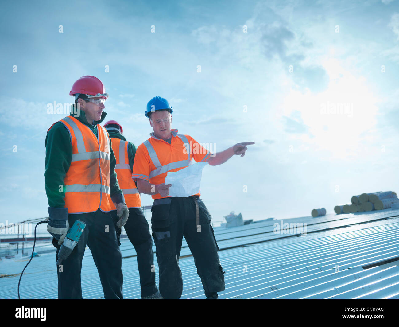 Workers reading blueprints on roof - Stock Image