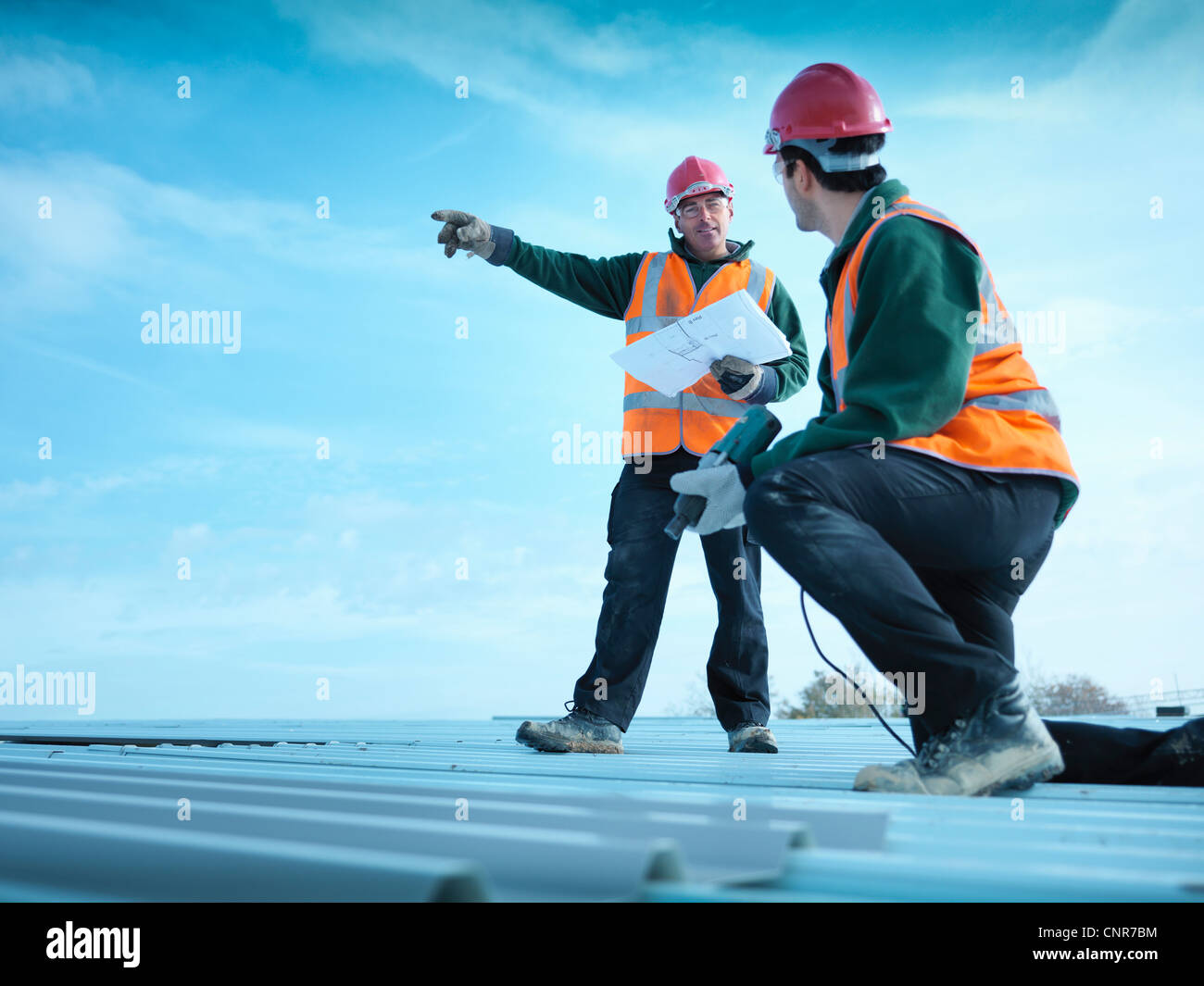 Workers reading blueprints on roof Stock Photo