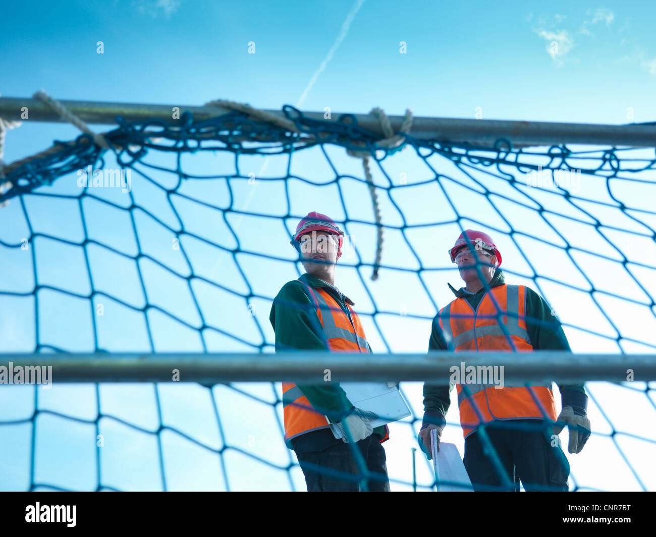 Workers standing behind fence netting - Stock Image