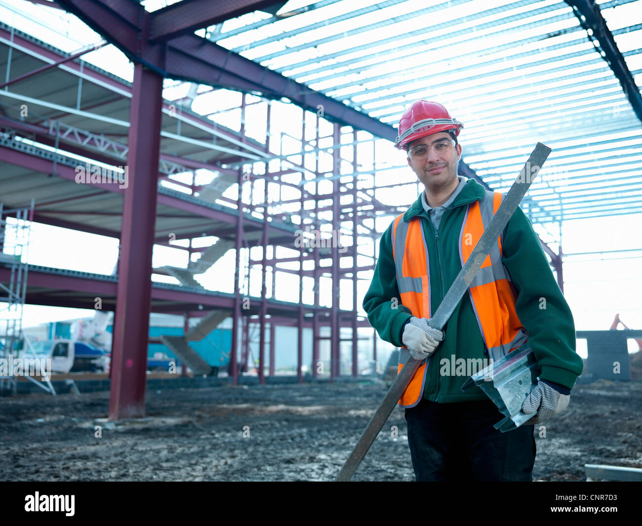 Construction worker holding pole - Stock Image