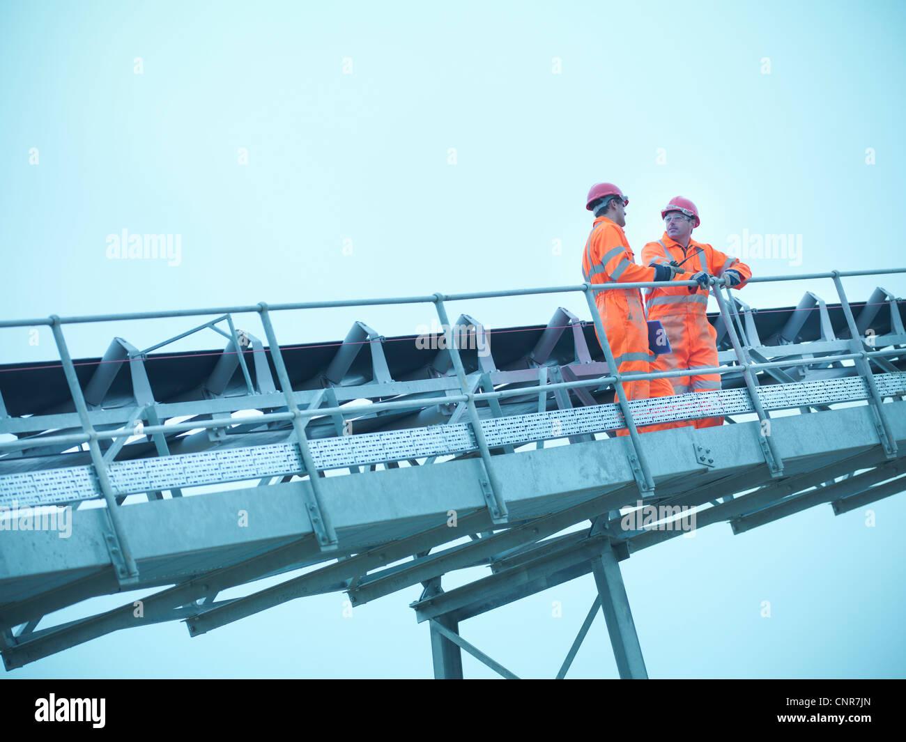 Worker climbing screening conveyor - Stock Image