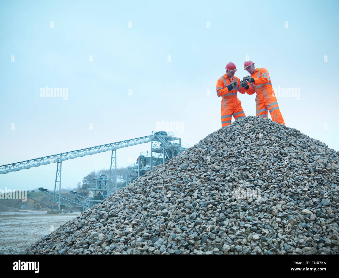 Workers inspecting quarry rocks - Stock Image