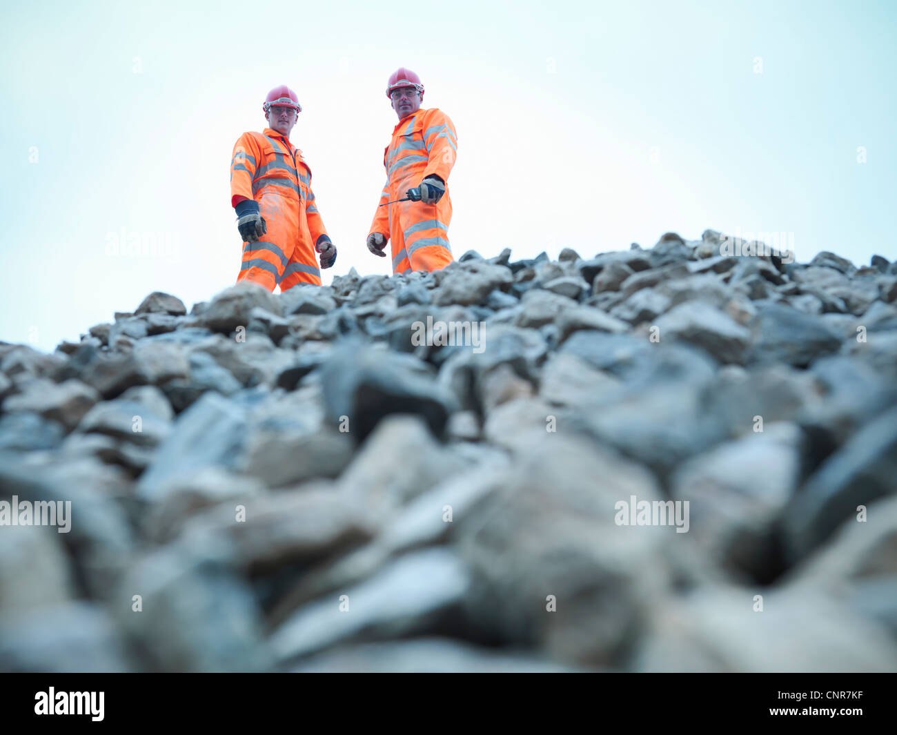 Workers standing on quarry rock pile - Stock Image