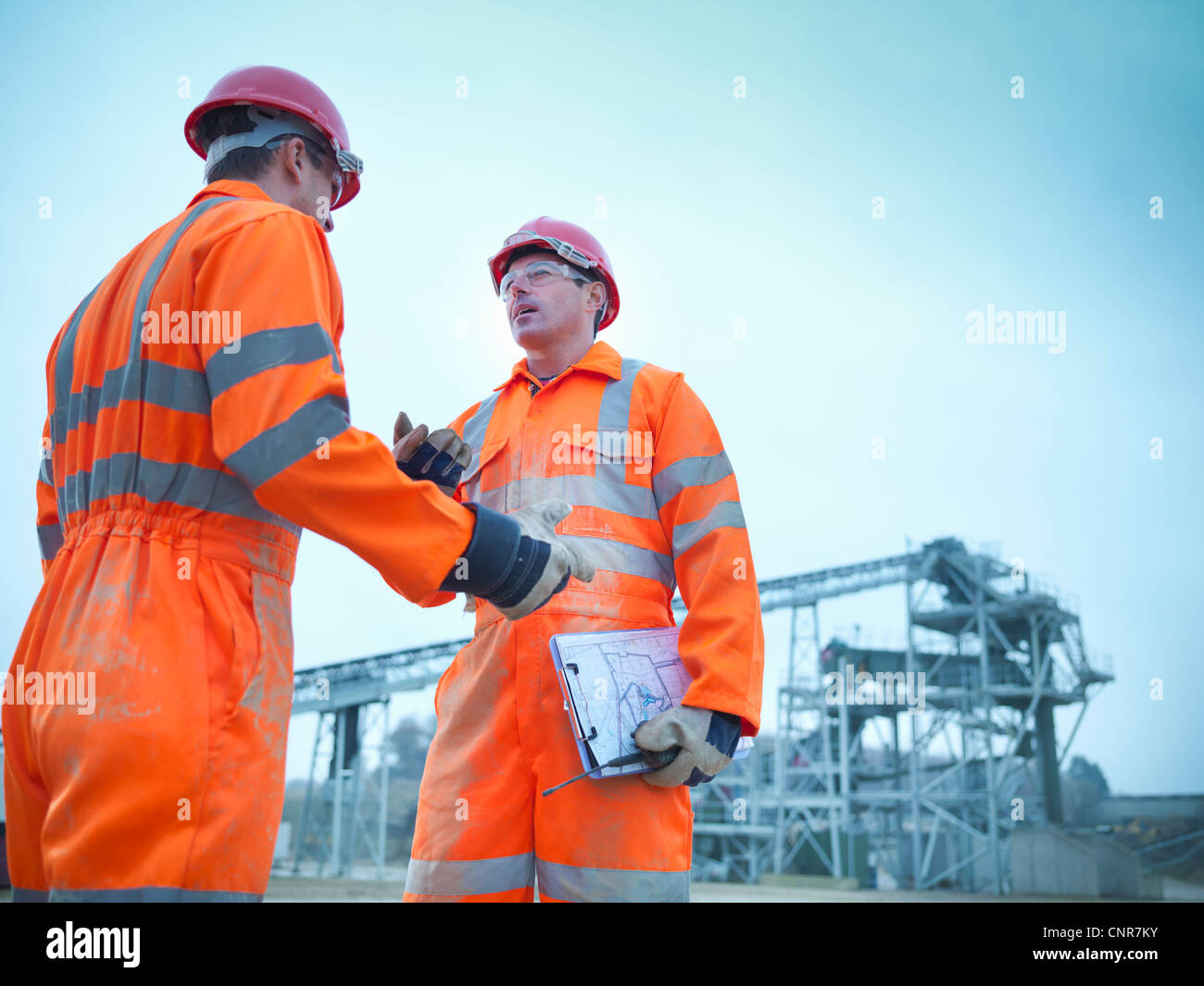 Workers talking at quarry - Stock Image