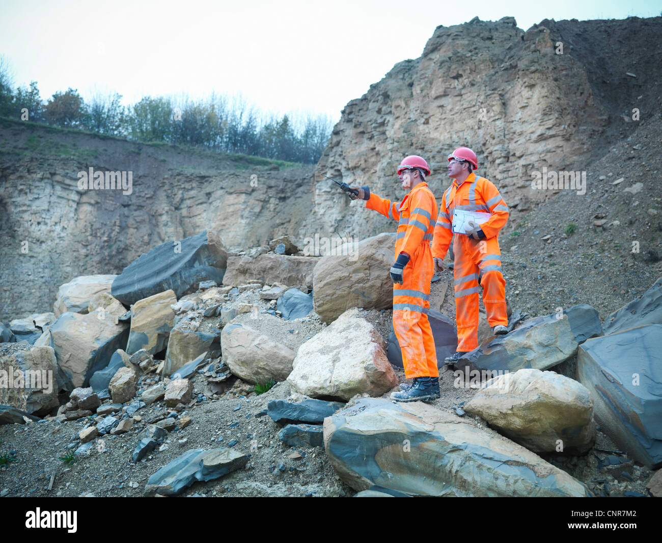Workers examining rocks in quarry - Stock Image