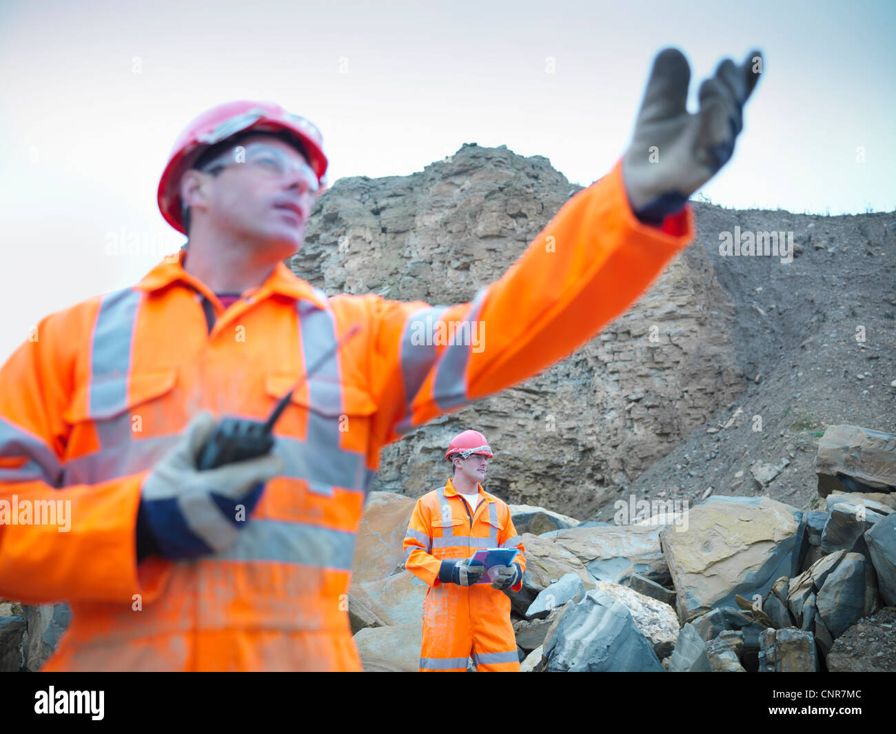 Workers standing in stone quarry - Stock Image