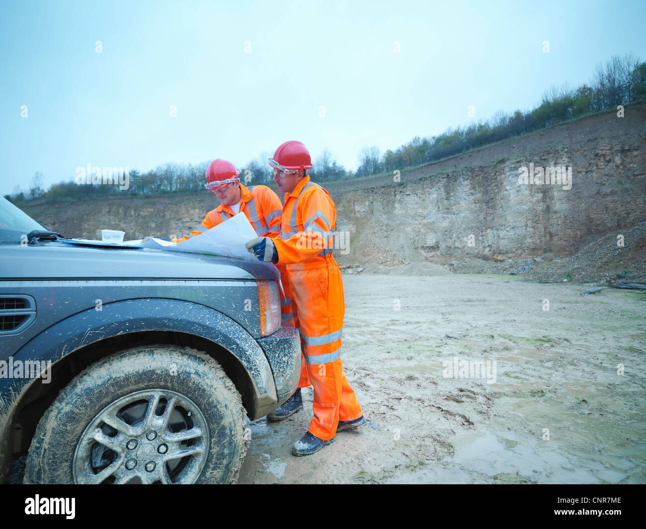Workers reading blueprints in quarry - Stock Image