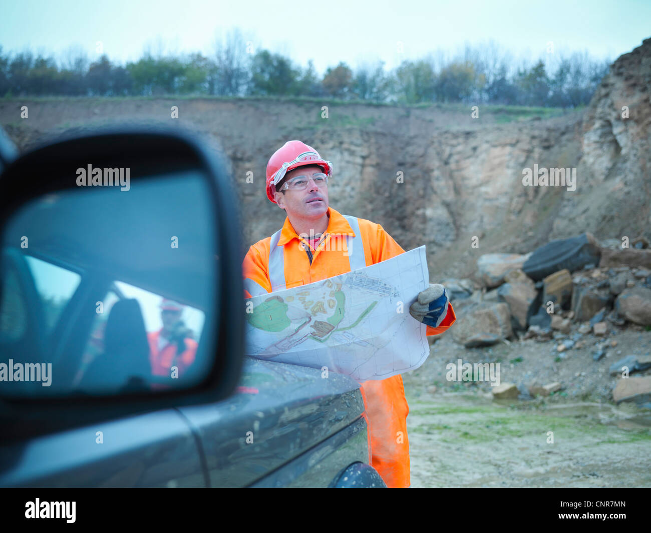 Workers reading blueprints in quarry Stock Photo