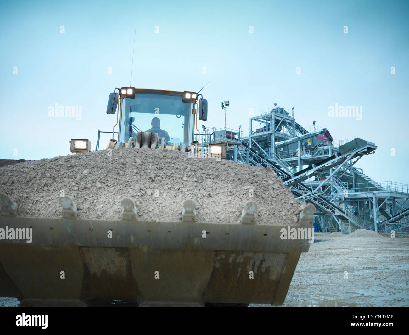Worker driving digger with gravel - Stock Image