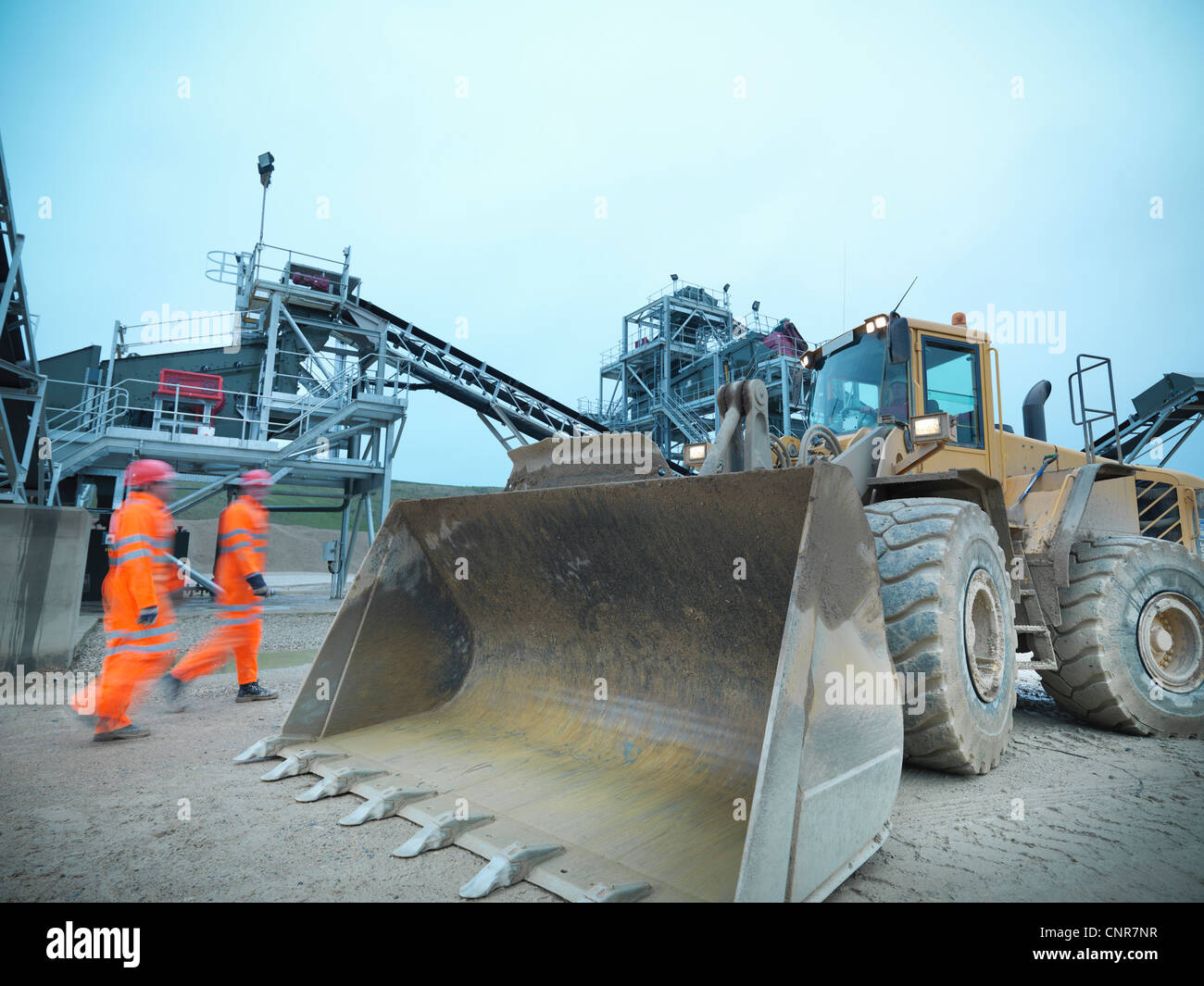 Blurred view of workers walking on site - Stock Image