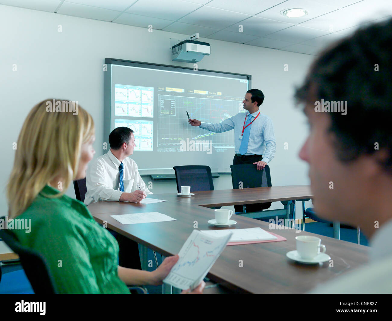 Businessman using projection in meeting Stock Photo