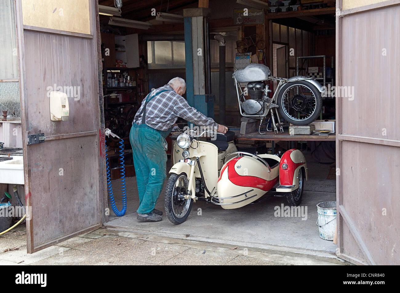 mechanic moving a restored vintage Moto Guzzi in a restoration workshop - Stock Image