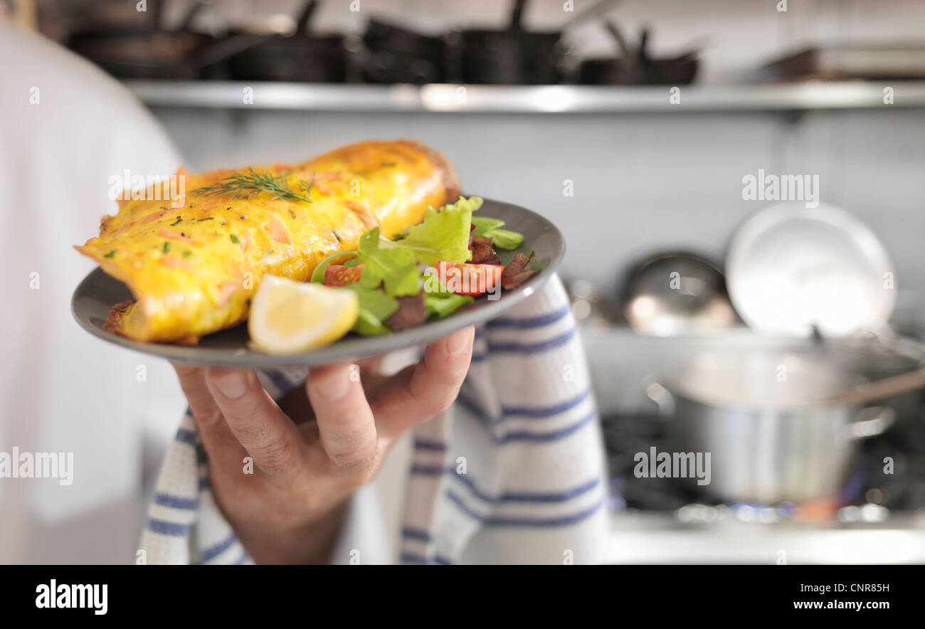 Chef holding salmon omelet and salad - Stock Image