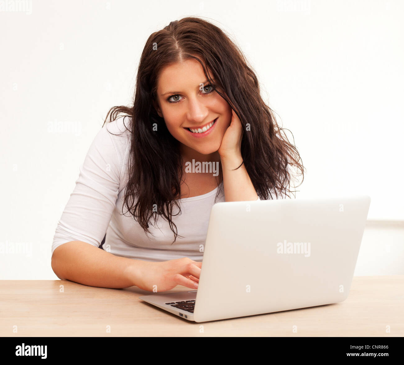 Portrait of a smiling woman using her laptop, isolated on white background Stock Photo