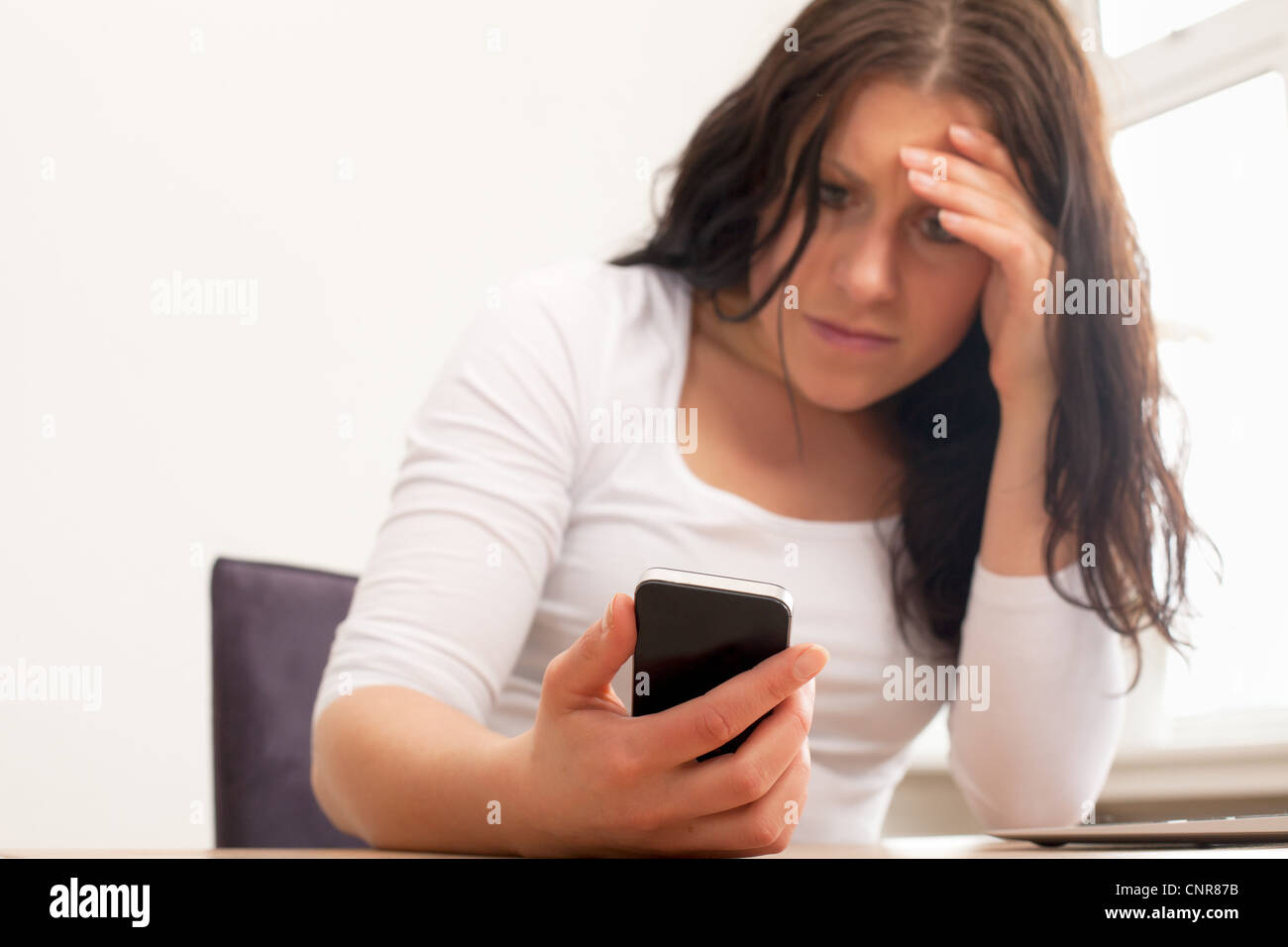 Portrait of an upset woman reading a text message on her phone - Stock Image