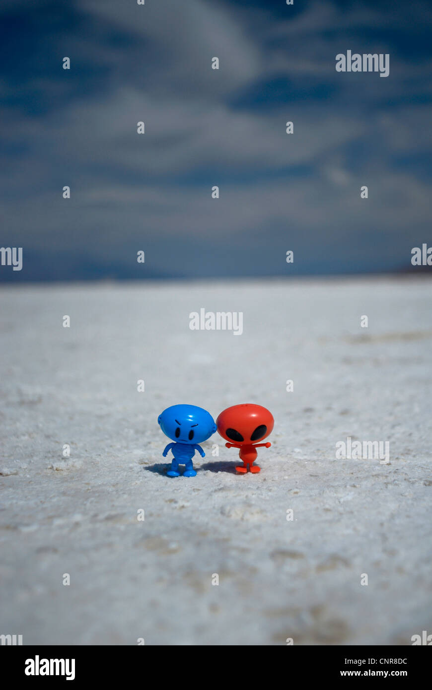 Toy alien figures on dirt path - Stock Image