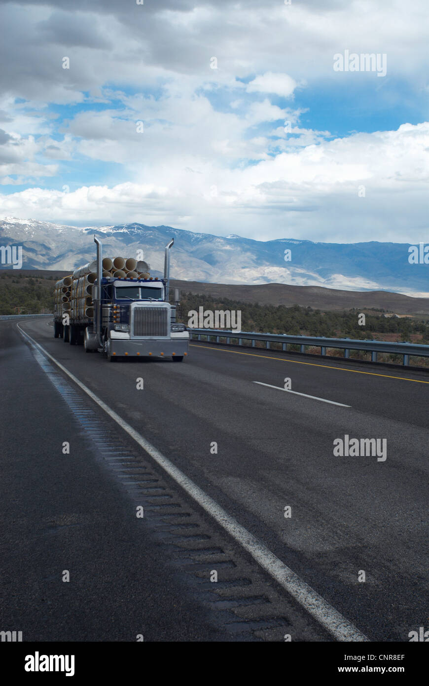 Truck carrying logs in rural landscape - Stock Image