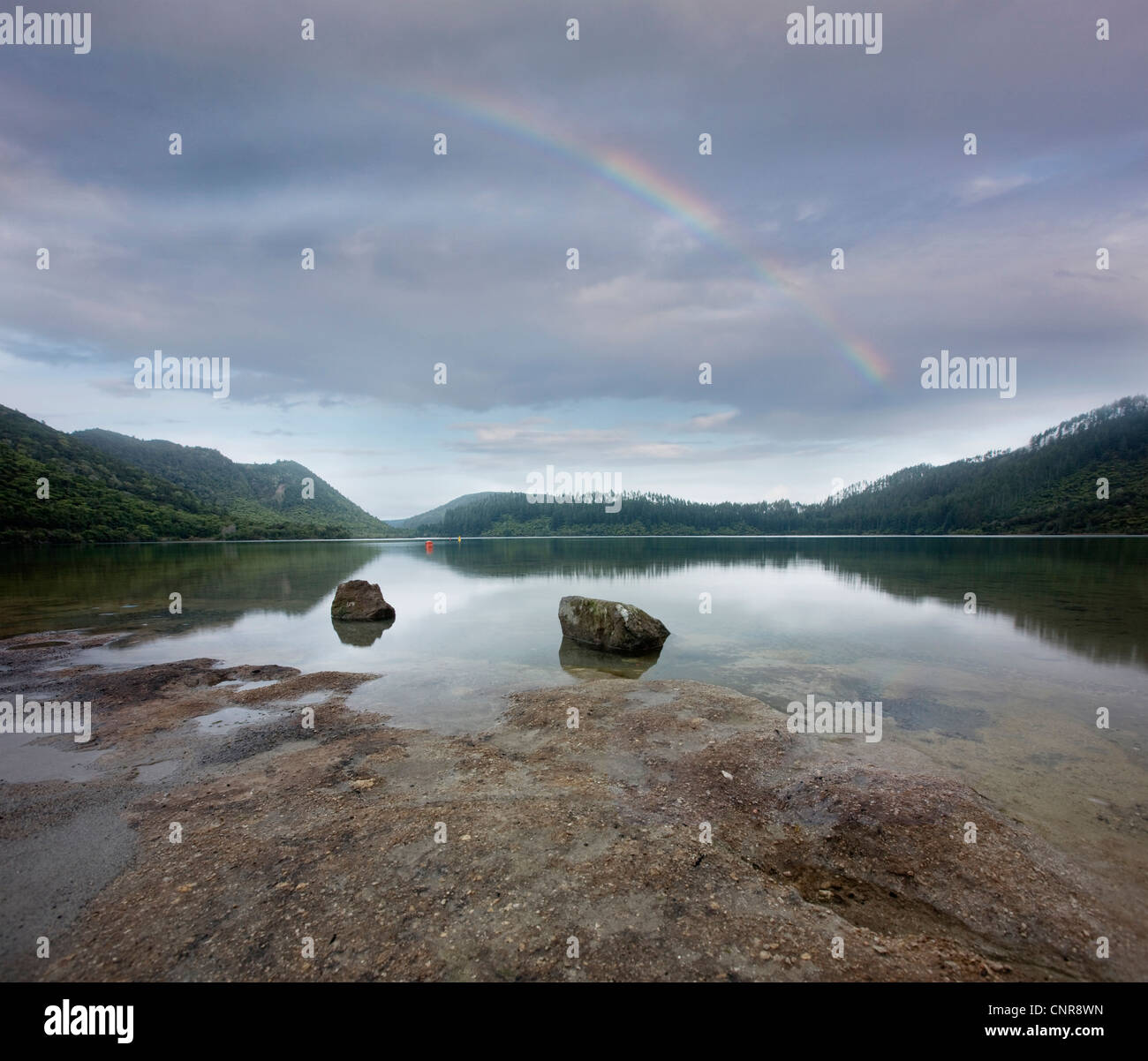 Rainbow stretching over rocky beach - Stock Image