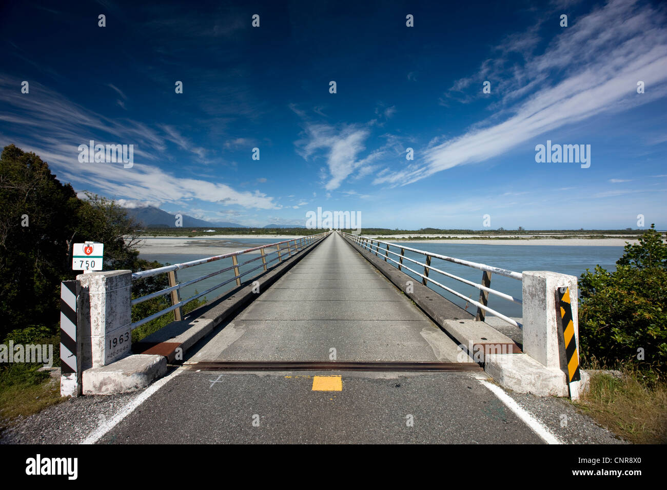 Bridge stretching over rural river Stock Photo