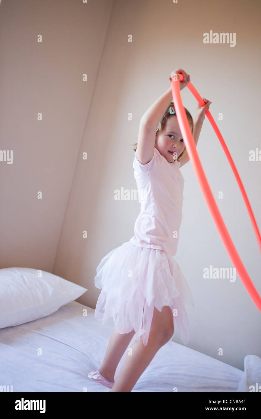 Girl playing with hula hoop in bedroom - Stock Image