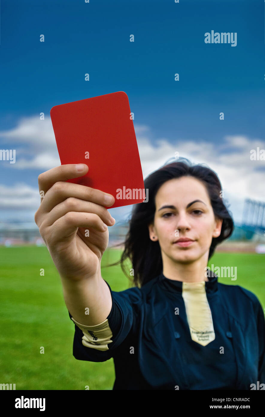 Woman holding red card on soccer pitch - Stock Image
