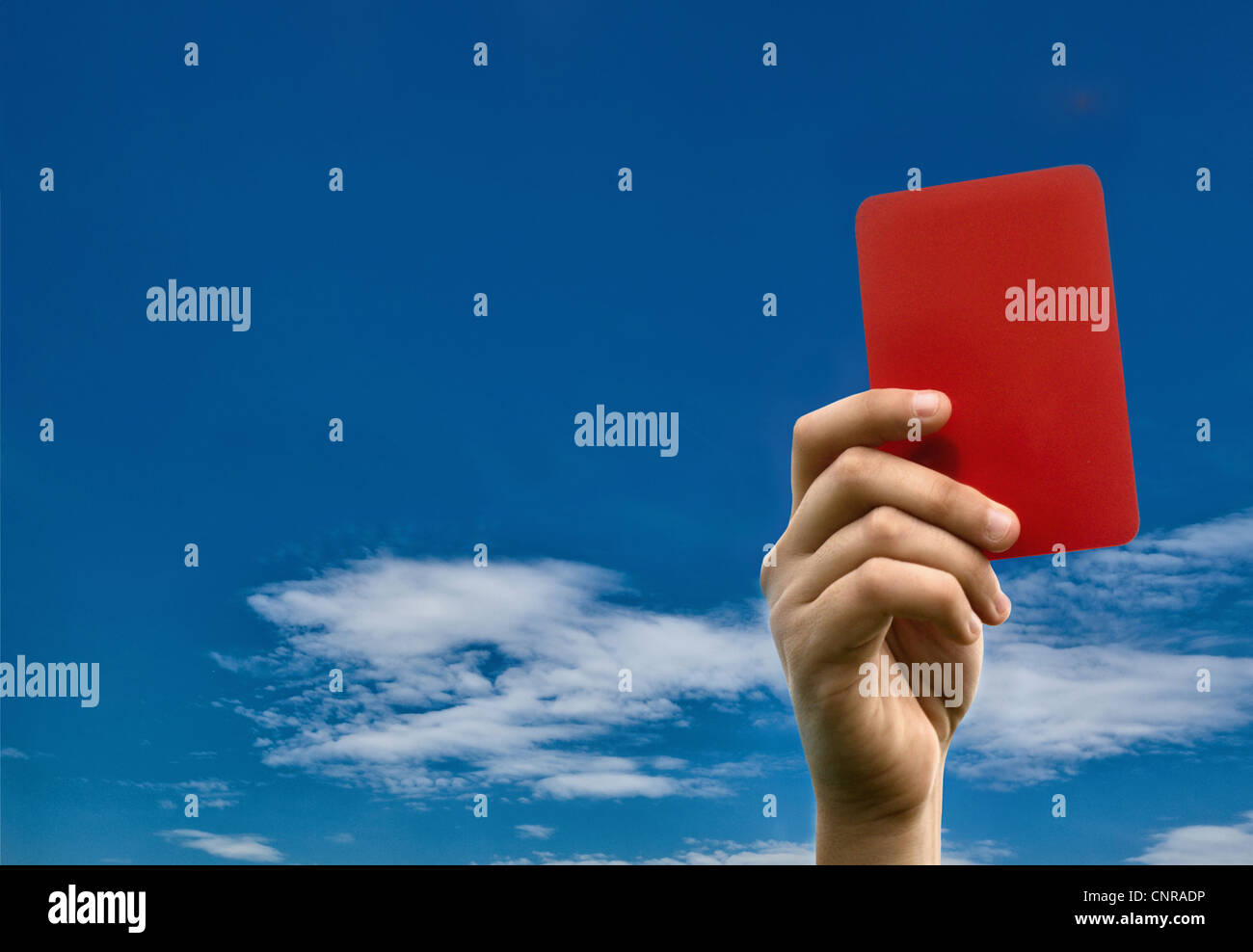Hand holding red card against blue sky - Stock Image