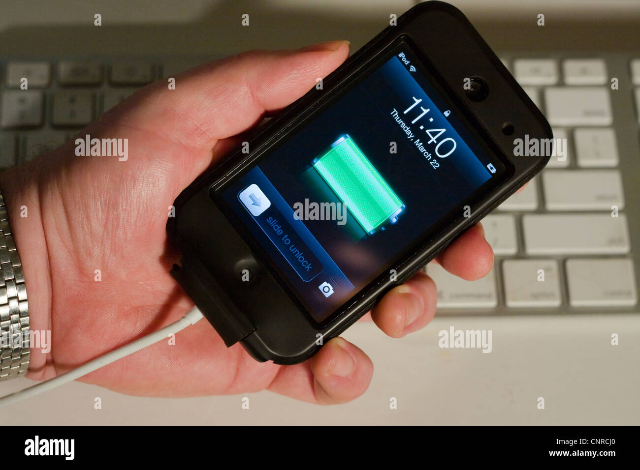 Man's hand holding an iPod Touch showing a fully charged