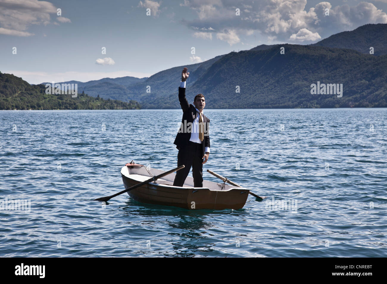 Businessman calling for help in rowboat - Stock Image