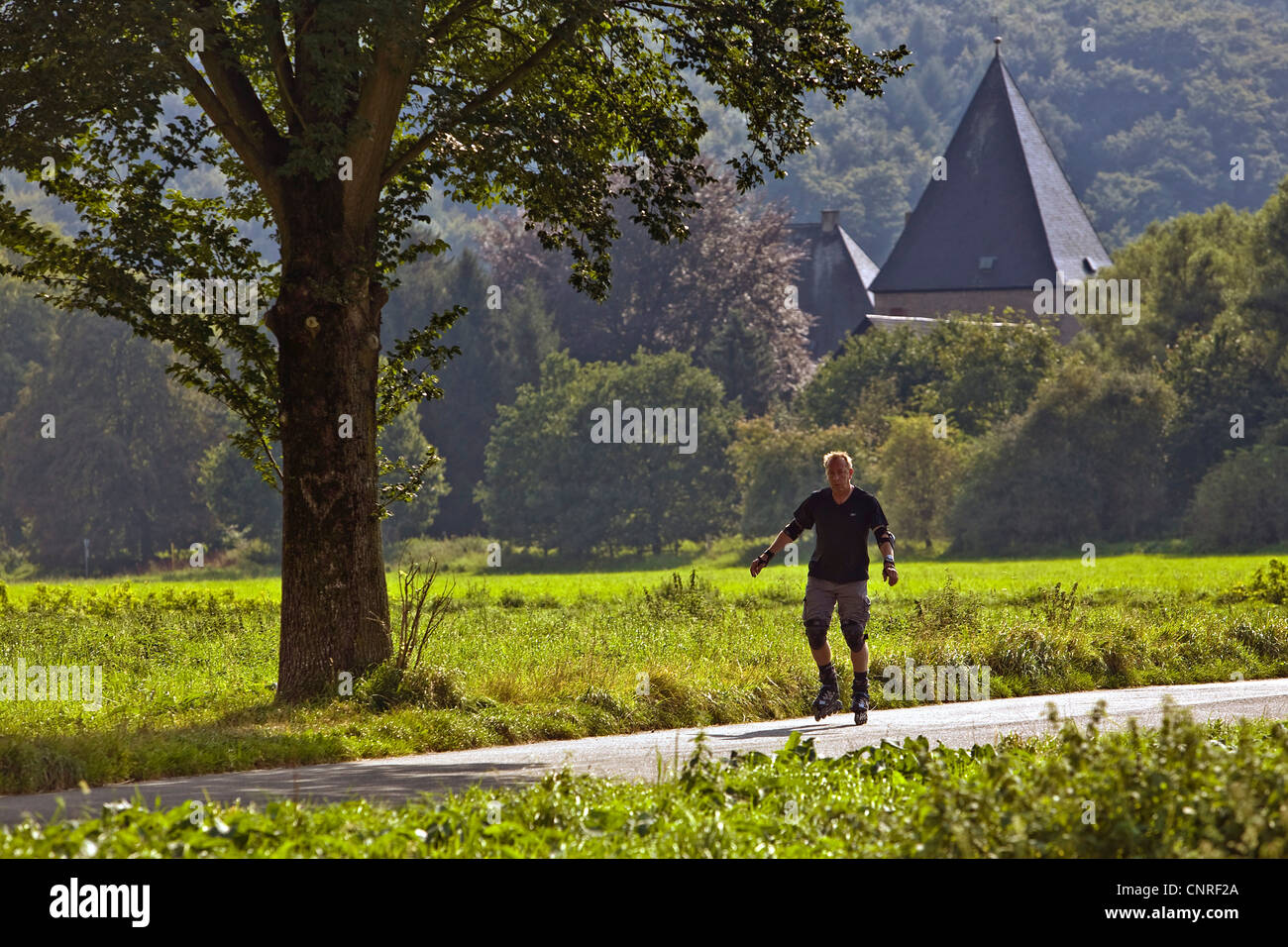 Inline slater on the Ruhr Valley Cycleway, Kemnade castle in the background, Germany, North Rhine-Westphalia, Ruhr - Stock Image