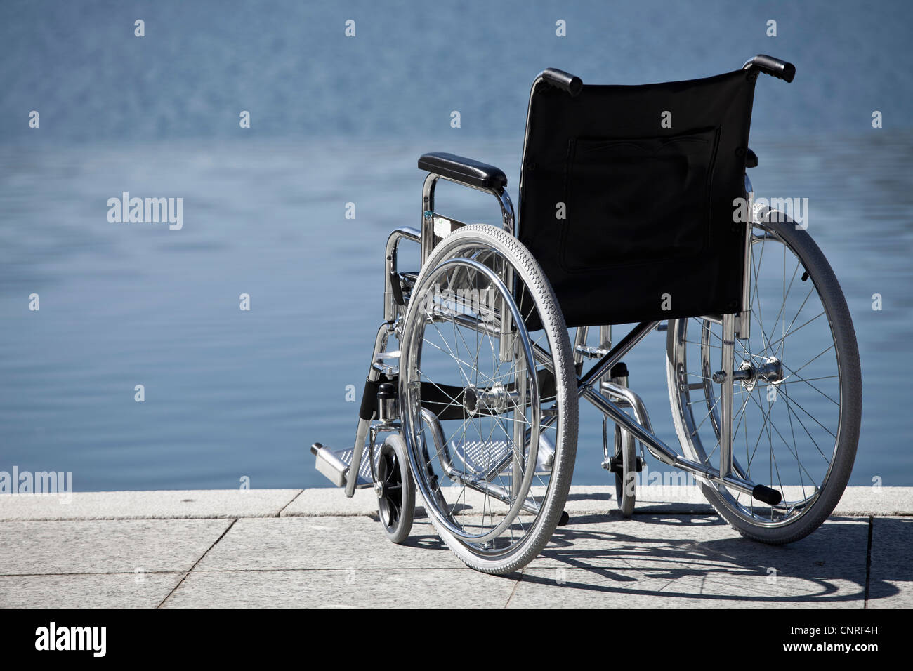 Wheelchair parked by water Stock Photo