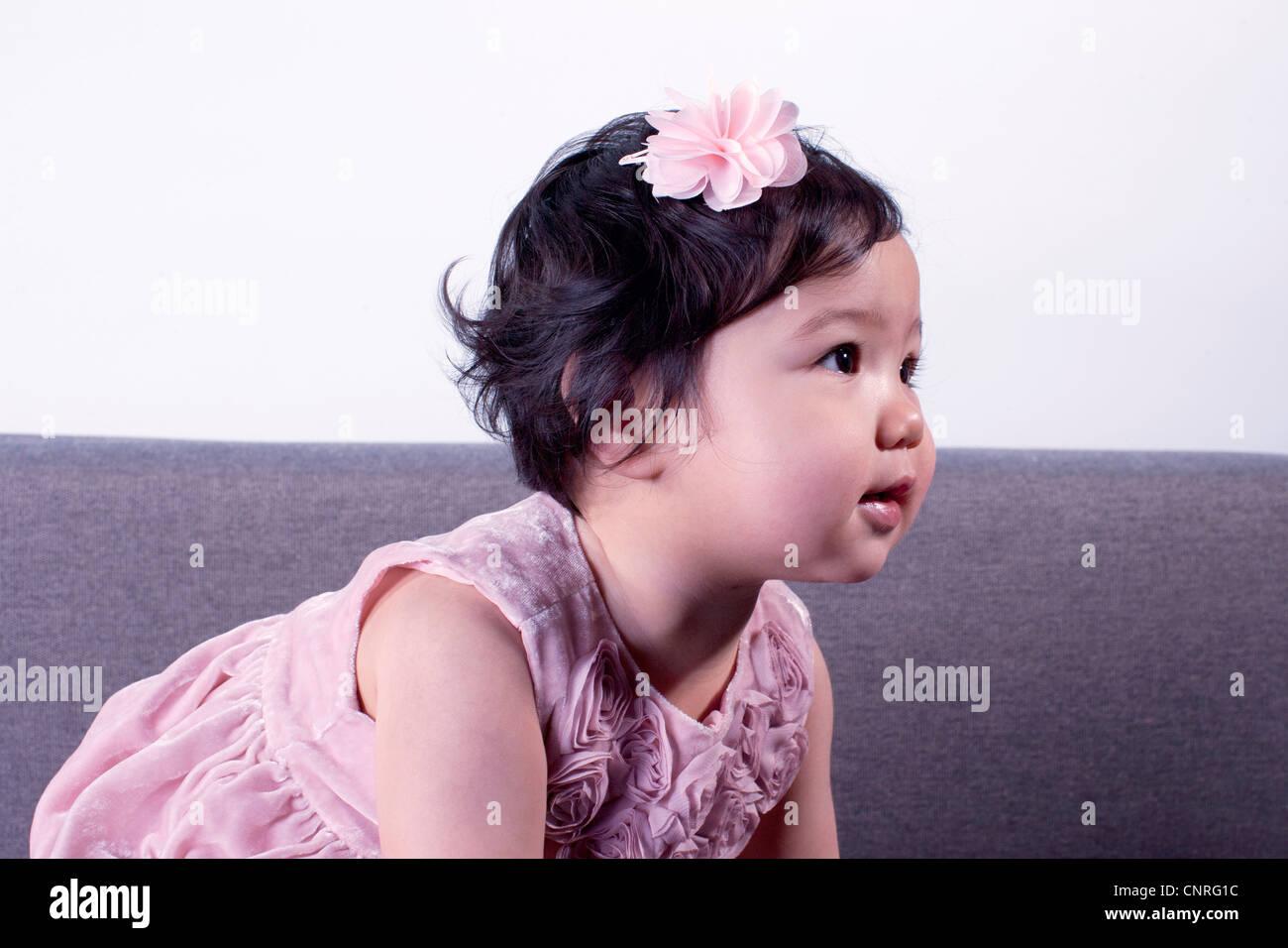 Infant girl looking away - Stock Image