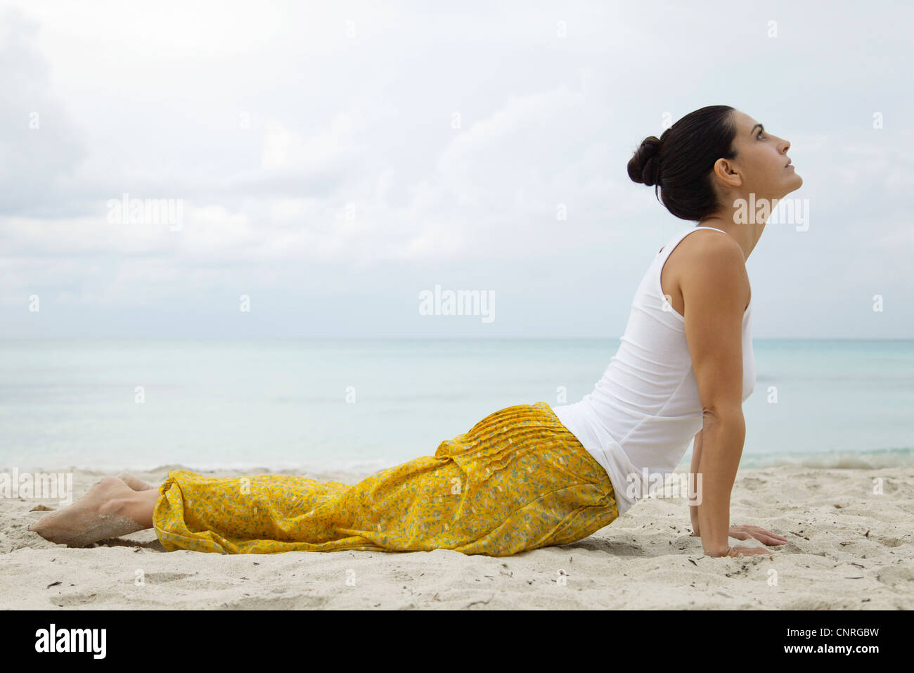 Mature woman in cobra pose on beach, side view - Stock Image