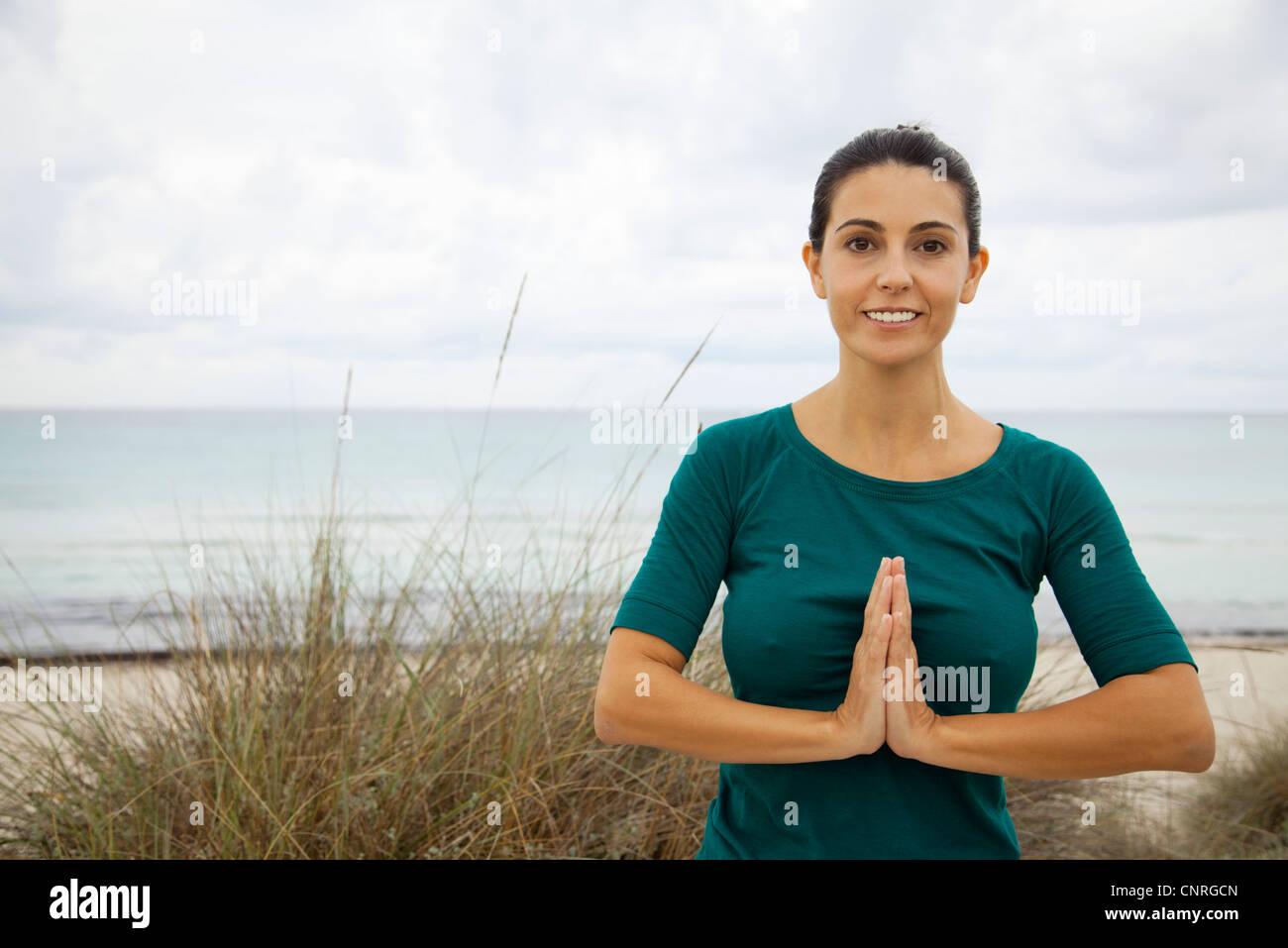 Mature woman practicing yoga on beach, portrait - Stock Image