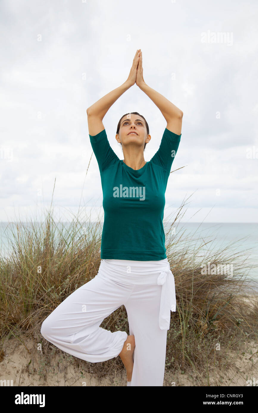 Mature woman in tree pose on beach, portrait - Stock Image