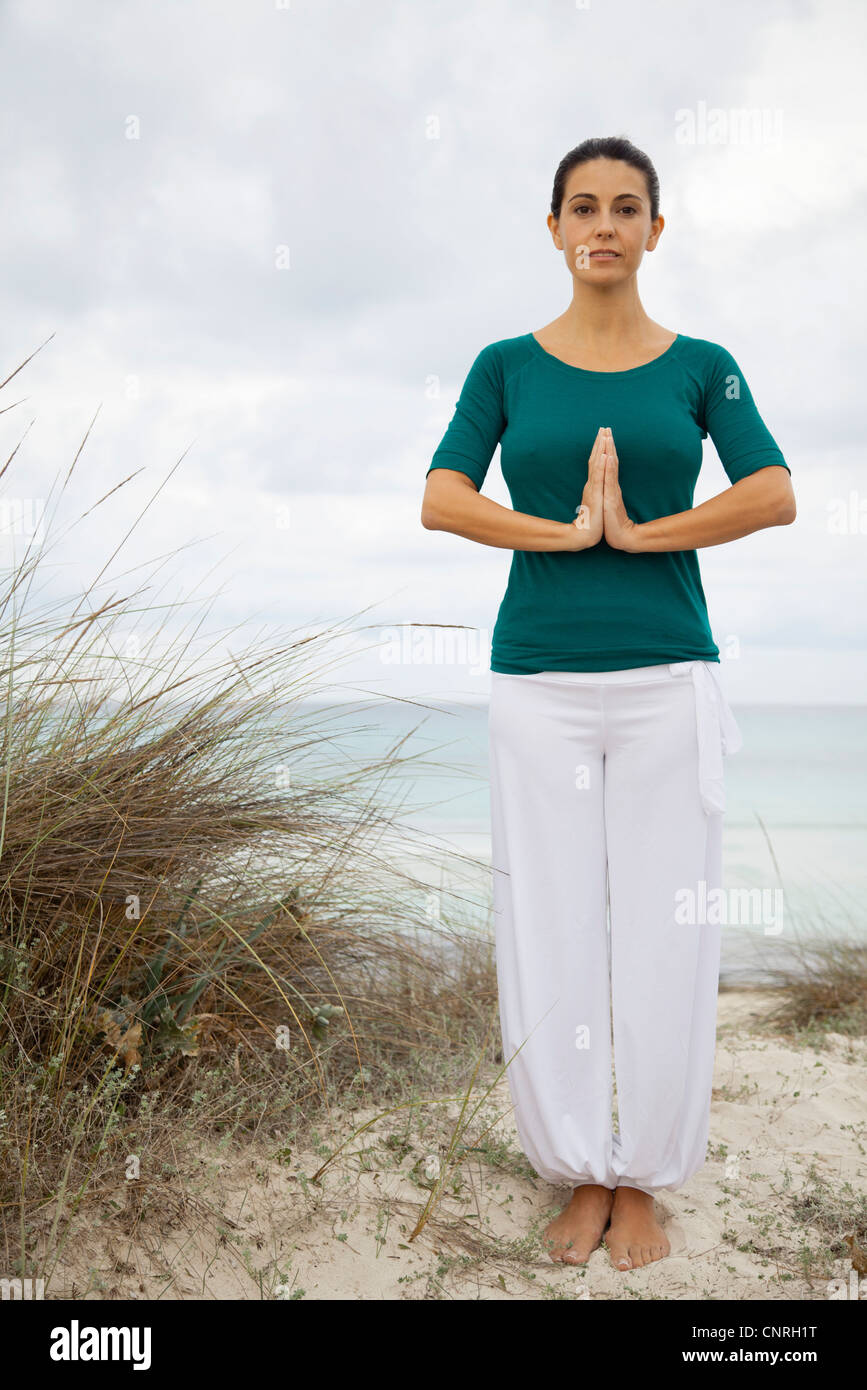 Mature woman in yoga prayer position on beach, portrait - Stock Image