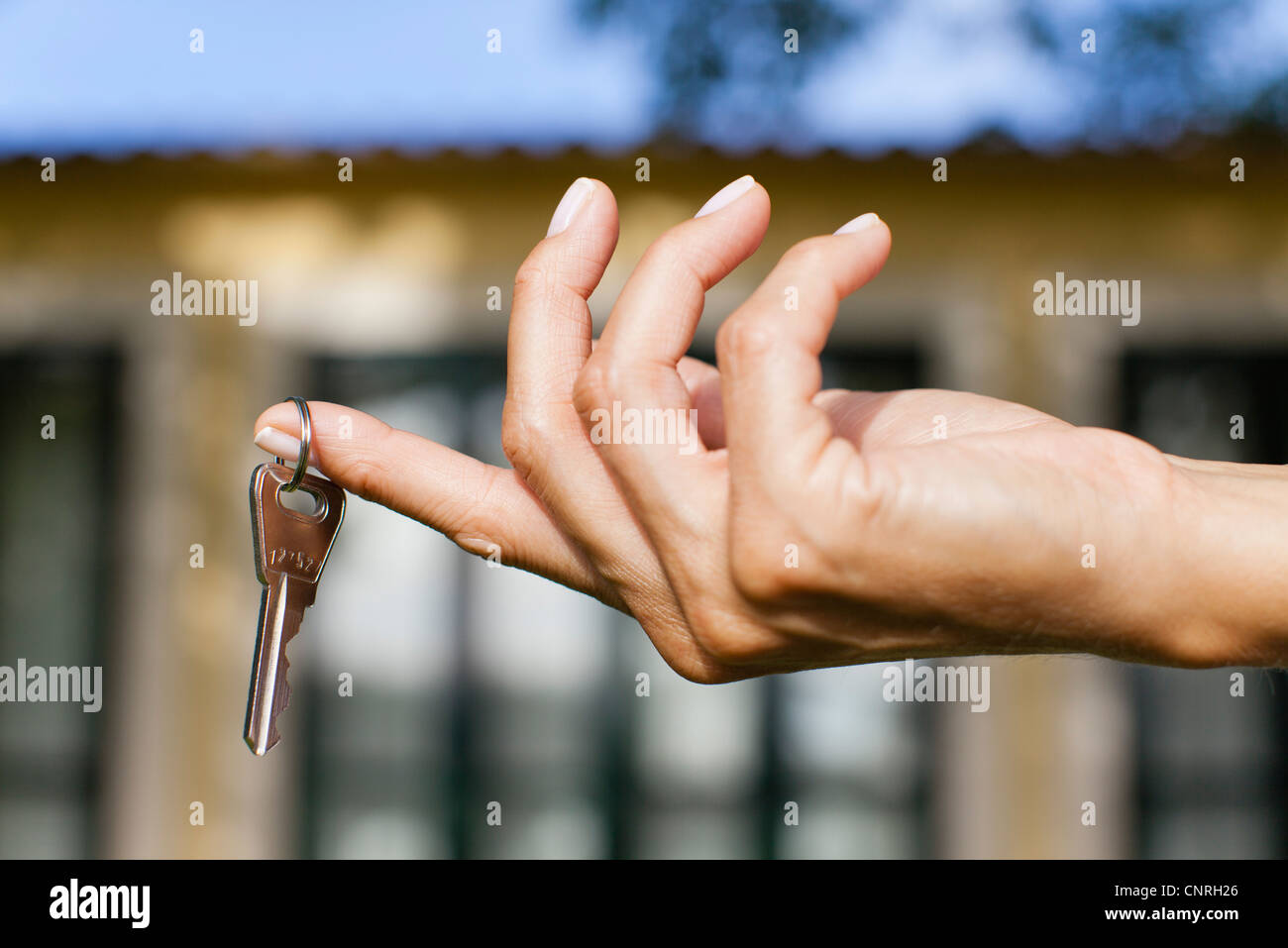 Woman's hand holding key, cropped - Stock Image