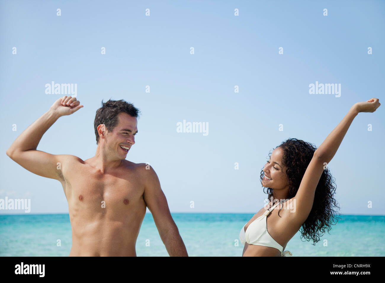 Couple stretching together at the beach - Stock Image
