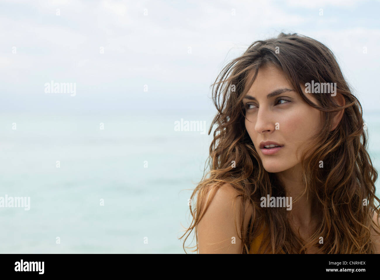Young woman looking over shoulder, portrait - Stock Image