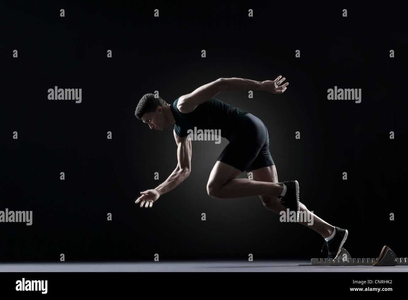 Runner leaving starting block - Stock Image