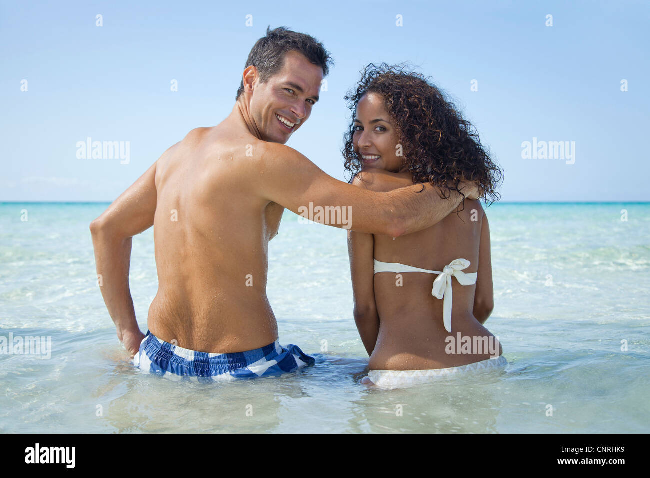 Couple waist deep in water at the beach, smiling over shoulders at camera - Stock Image
