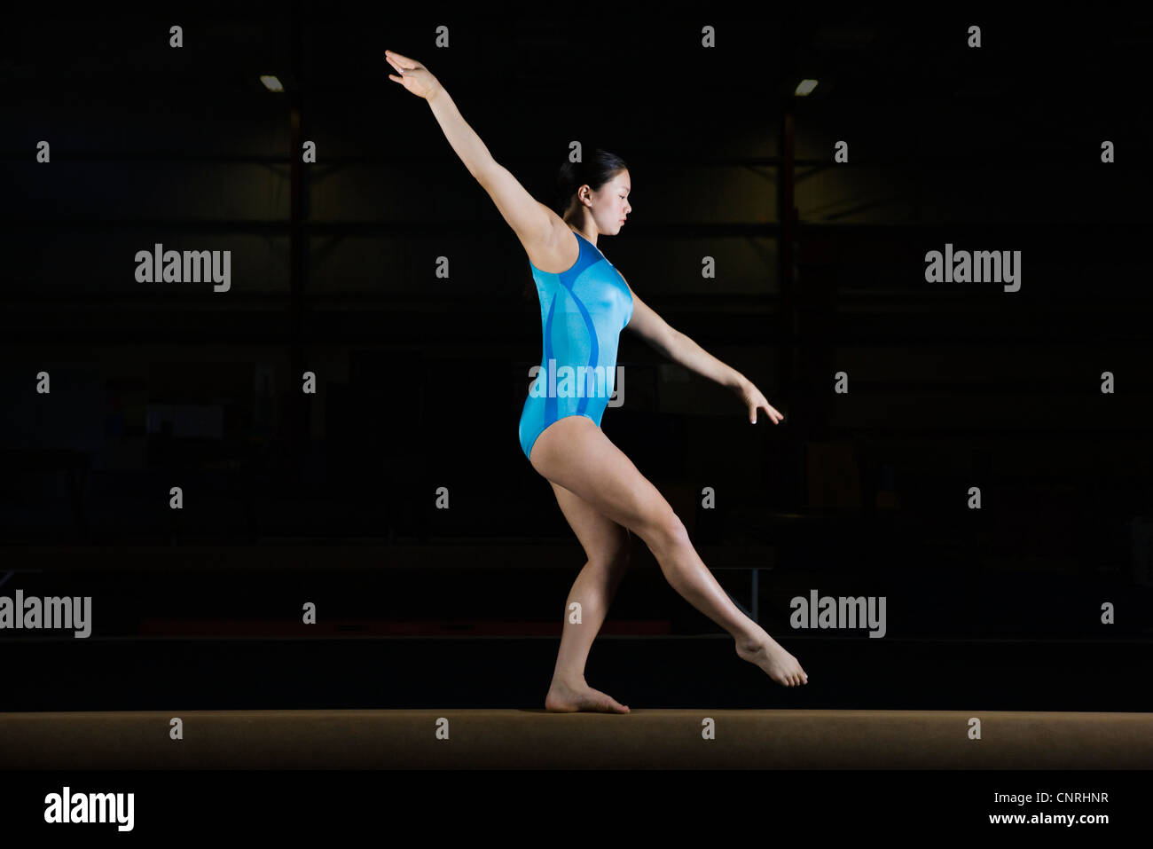 Teenage girl gymnast performing on balance beam - Stock Image