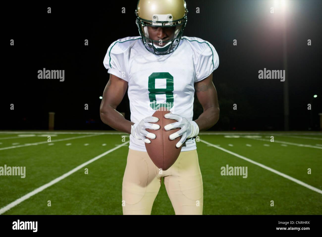 Football player holding football Stock Photo