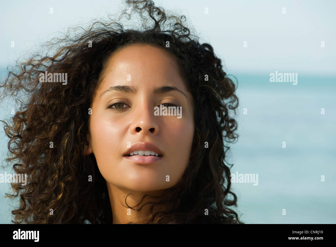 Woman with hair tousled by breeze, portrait - Stock Image
