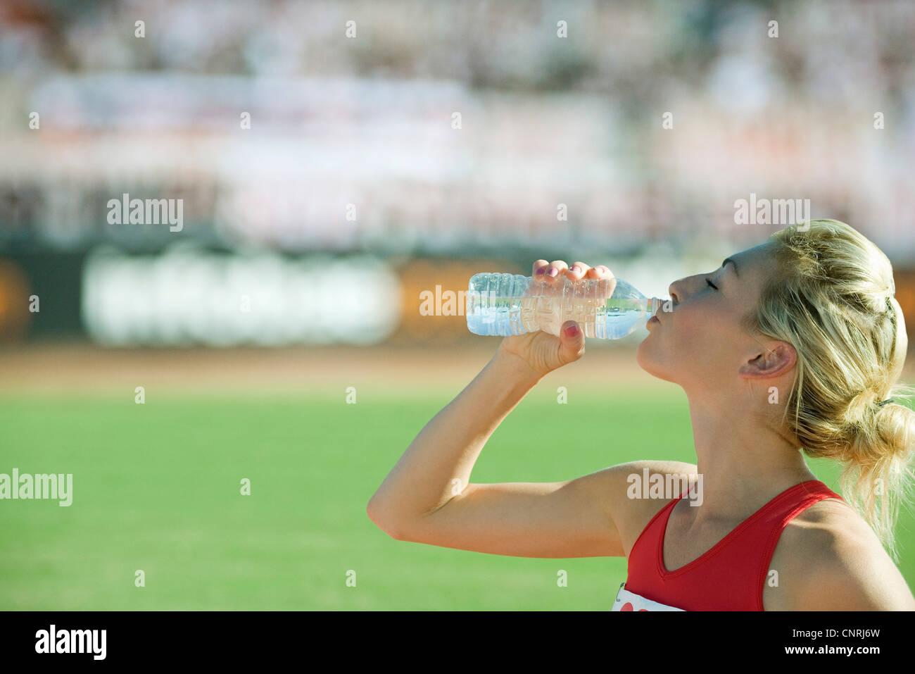 Female athlete drinking bottled water - Stock Image