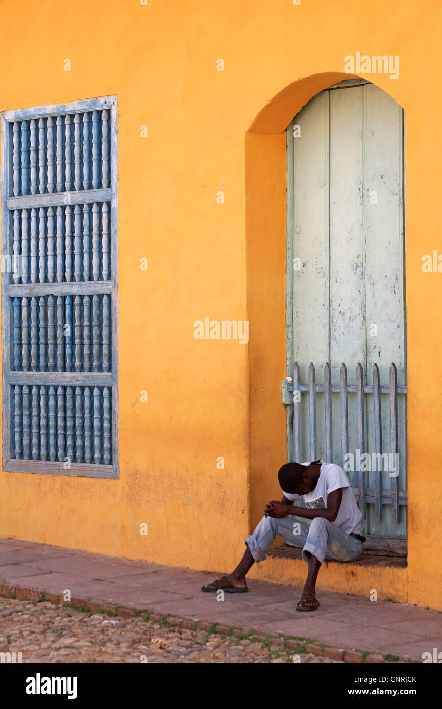 Daily life in Cuba - Afro-Caribbean man sat on doorstep of brightly coloured building looking down at Trinidad, - Stock Image