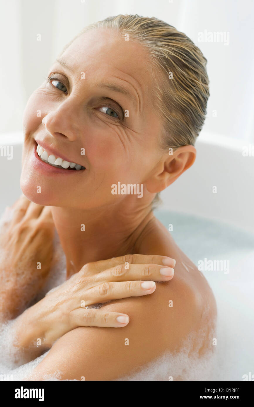 Mature woman enjoying bubble bath - Stock Image