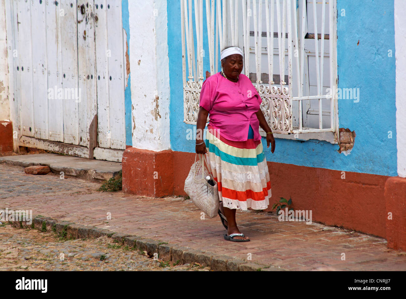 Daily life in Cuba - Afro-caribbean woman wearing bright coloured clothing carrying shopping down street at Trinidad, - Stock Image