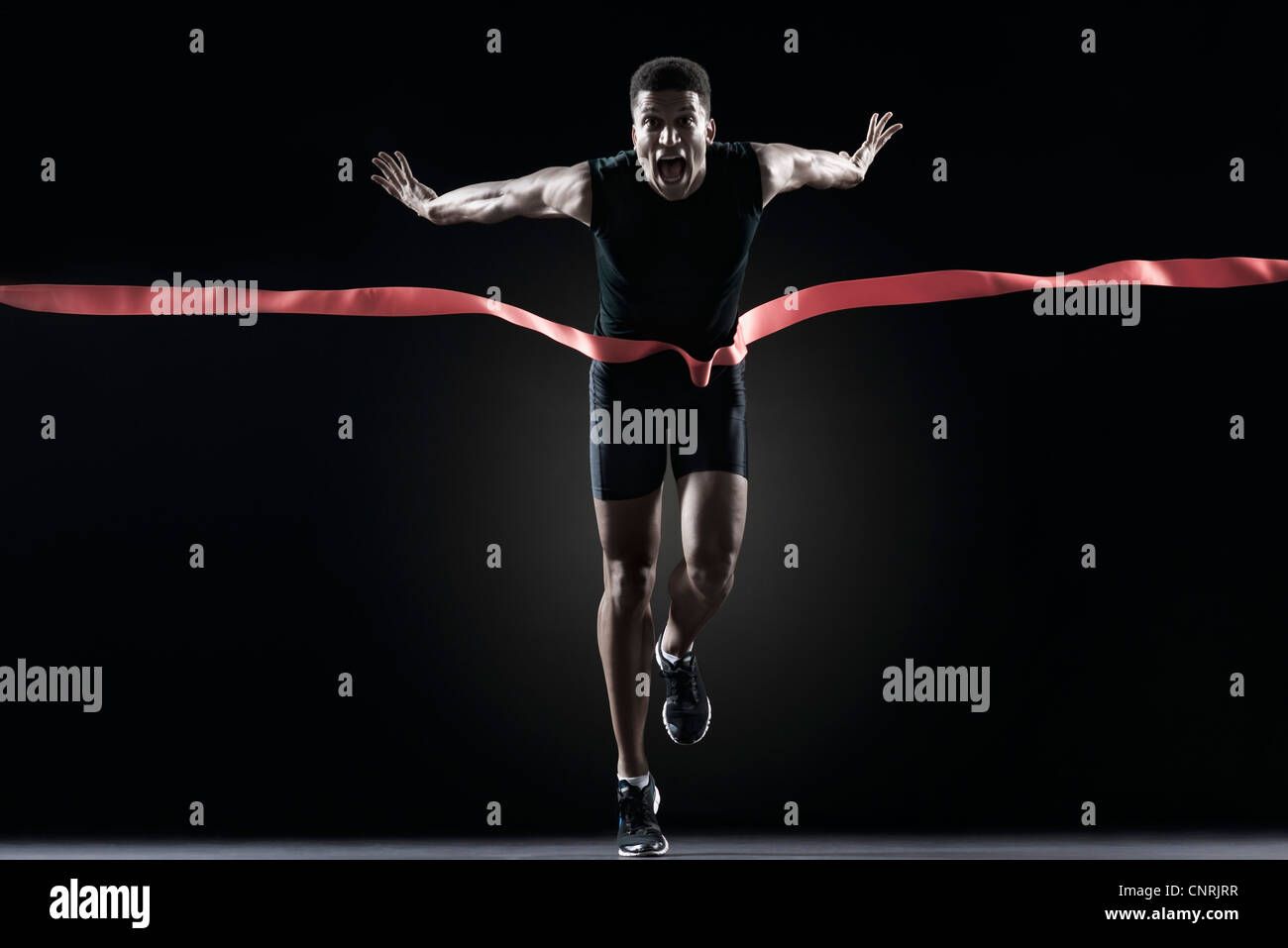 Runner crossing finishing line - Stock Image