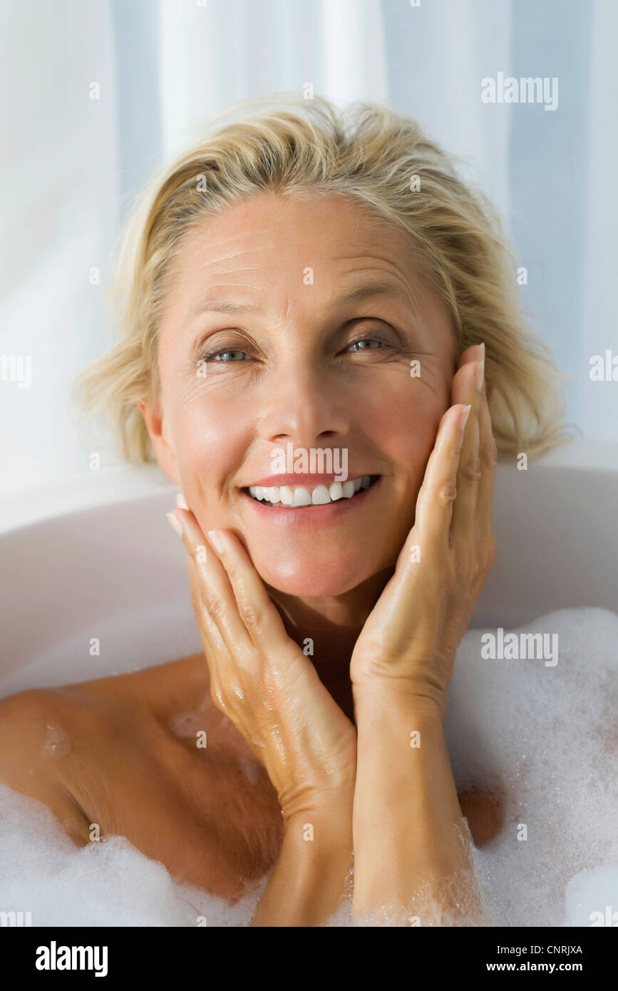 Mature woman enjoying bubble bath, portrait - Stock Image